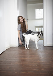Young woman with dog at home on the phone - RHF000741