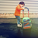 Boy, with suitcase on wheels, standing in a puddle, Erkrath, North Rhine-Westphalia, Germany - SBD002766