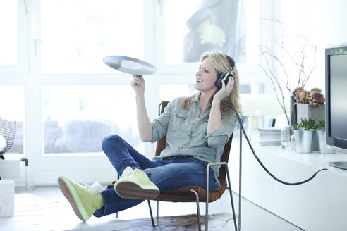 Woman holding record hearing music with headphones at home - MAEF010065