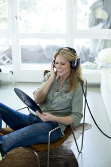 Woman holding record hearing music with headphones - MAEF010046