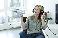 Woman holding record hearing music with headphones - MAEF010047