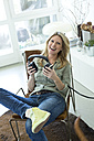 Potrait of smiling woman with headphones at home - MAEF010053