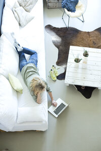 Woman relaxing on couch using laptop - MAEF010057