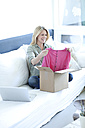 Woman sitting on couch unpacking online shopping purchase - MAEF010075