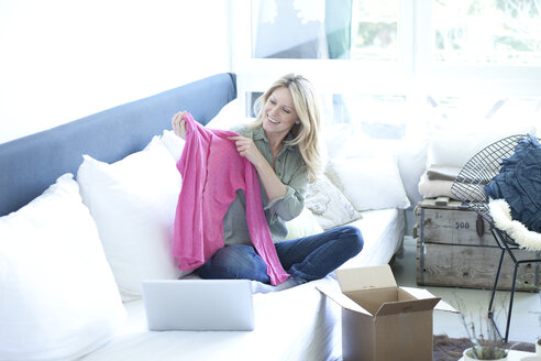 Woman sitting on couch unpacking online shopping purchase - MAEF010069