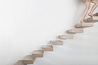 Woman walking on floating staircase - PDF000898