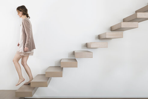 Woman walking on floating staircase - PDF000900