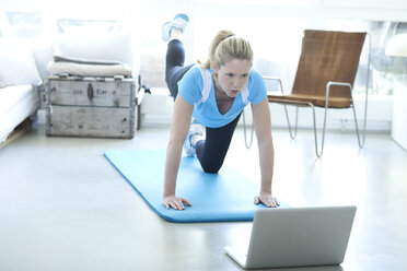 Woman looking at laptop exercising on gym mat in living room - MAEF010078