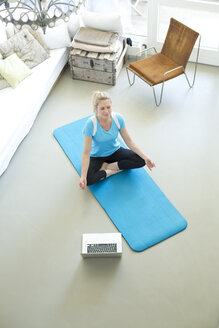 Woman with laptop practicing yoga on gym mat in living room - MAEF010093