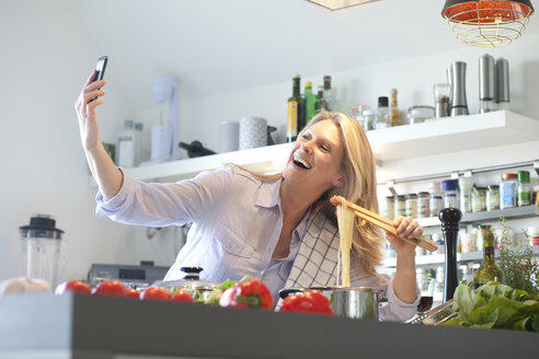 Happy woman cooking in kitchen taking a selfie - MAEF010113