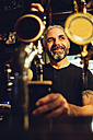 Man tapping beer in an Irish pub - MBEF001380