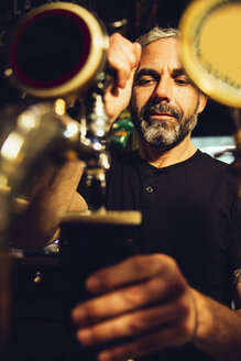 Portrait of a man tapping beer in an Irish pub - MBEF001381