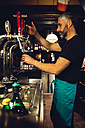 Man tapping beer in an Irish pub - MBEF001382