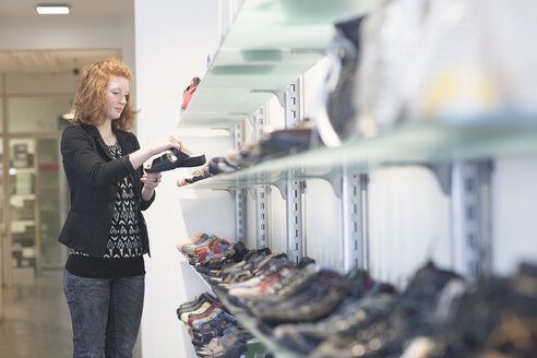 Young woman in shoe shop looking at sandal - SGF001434