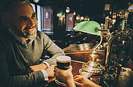Smiling man sitting at counter of a pub - MBEF001368