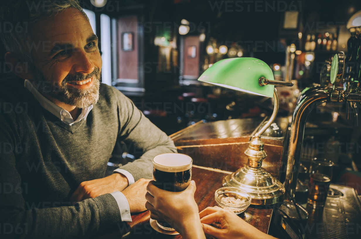 Smiling man sitting at counter of a pub - MBEF001368 - Martin Benik/Westend61