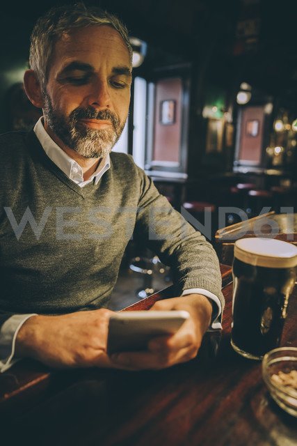 Portrait of man sitting at counter of a pub using smartphone - MBEF001354 - Martin Benik/Westend61