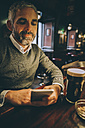 Portrait of man sitting at counter of a pub using smartphone - MBEF001354