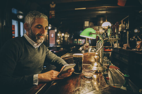 Man sitting at counter of a pub using smartphone - MBEF001355