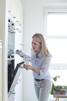 Woman in kitchen looking into oven - MAEF010123