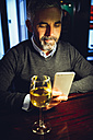 Portrait of man sitting at counter of a pub using smartphone - MBEF001359