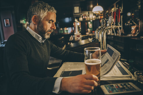 Man sitting at counter of a pub reading newspaper - MBEF001362
