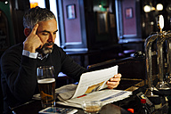 Man sitting at counter of a pub reading newspaper - MBEF001372