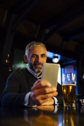 Man sitting at counter of a pub looking at his smartphone - MBEF001364