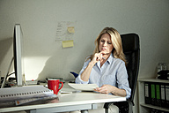 Woman sitting at desk at home looking at document - MAEF010097