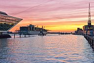 Germany, Hamburg, container ship and Dockland building at sunset - RJF000415