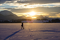 Germany, Hopfensee, woman strolling in winter landscape at sunset - WGF000629
