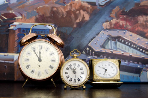 Old-fashioned alarm clocks in front of painting - GIS000084