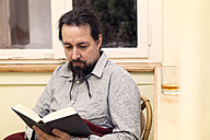 Man with braided beard reading book - MIDF000225