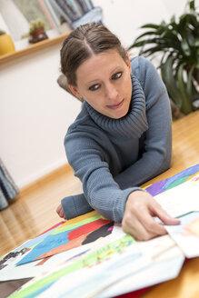 Woman lying on floor looking at children's paintings - MIDF000231