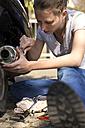Woman repairing motor scooter - MIDF000250