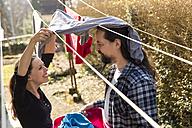 Playful couple hanging up laundry - MIDF000256