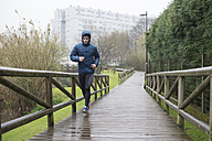 Spain, Galicia, Naron, runner on a promenade in park at a rainy day - RAEF000121