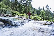 Austria, Altenmarkt-Zauchensee, young female hiker crossing a river - HHF005265