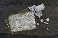 Metal box of different old mother-of-pearl buttons on dark wood - CRF002660