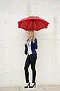 Smiling businesswoman with red umbrella leaning on concrete wall - BFRF001025
