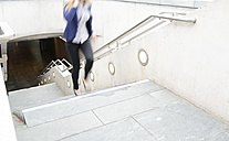 Telephoning businesswoman running upwards a staircase - BFRF001060