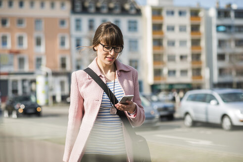 Young woman walking in street, using mobile phone - UUF003789