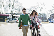 Happy couple going home together, woman riding bicycle - UUF003805