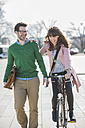 Happy couple going home together, woman riding bicycle - UUF003806