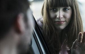 Couple saying farewell through windscreen - UUF003831