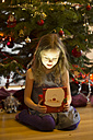 Little girl sitting in front of Christmas tree watching Christmas present - SARF001615