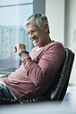 Smiling man with smartwatch sitting in a leather chair - RBF002574
