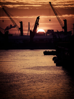 Germany, Hamburg, Silhouettes of harbour cranes at sunset, Koehlbrand bridge in the background - KRPF001411