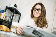 Portrait of smiling woman with newspaper - RZDF000002