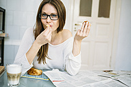 Woman with newspaper eating croissant - RZDF000004
